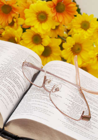 Open Bible with glasses and spring flowers in the background photo