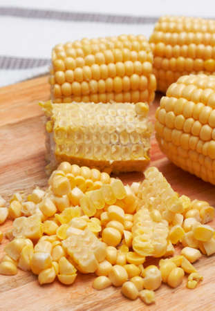 Sweet corn kernels being cut off from the cob on a wooden chopping board photo