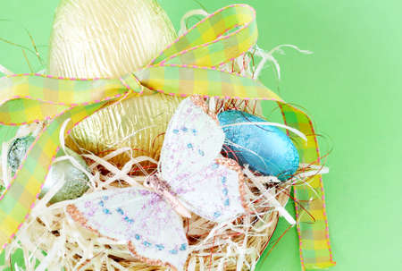 Assortment of chocolate Easter eggs wrapped in colorful paper with butterfly photo