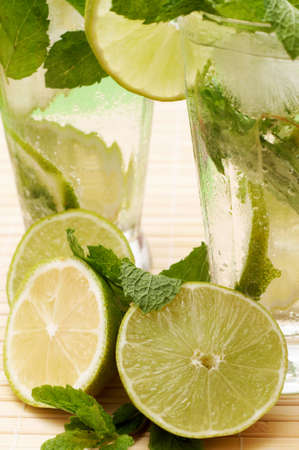 Two mojito cocktails with lime, lemons, mint leaves and ice on light wooden background
