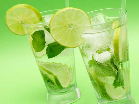 Two mojito cocktails with lime, mint leaves and ice on green background photo
