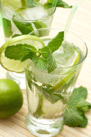 Two mojito cocktails with lime, mint leaves and ice
