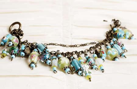 Fashionable colorful charm bracelet on cream linen background Stock Photo