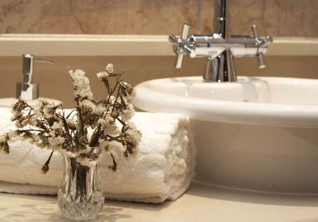 Beautiful stylish bathroom interior with white folded towel, white sink, bottle of liquid soap and some dry flowers Stock Photo