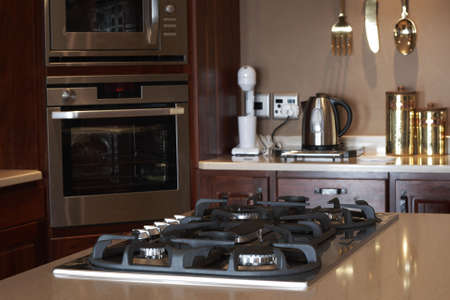 Modern kitchen interior with gas stove in focus and new oven in the background photo