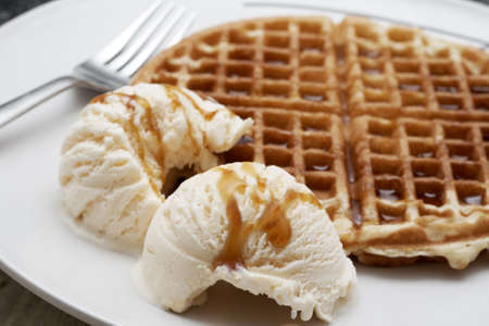 Freshly baked waffle with two scoops of vanilla ice-cream covered with syrup, served on a white plate Stock Photo