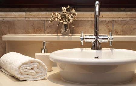 Beautiful évier dans une salle de bain avec serviette enroulée, à côté de lui et de fleurs Banque d'images