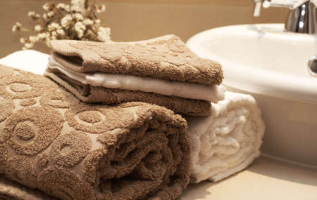 Stack of colorful brown and white towels on the table in the bathroom  Stock Photo