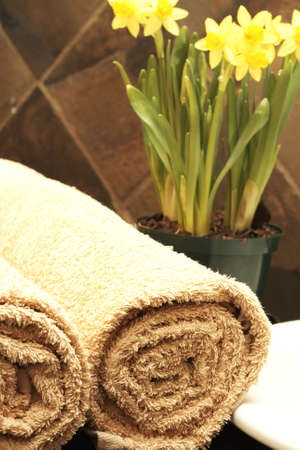 Beautiful modern bathroom with rolled up beige towels and bright yellow daffodil flowers Stock Photo - 3141189