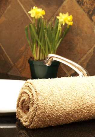 Beige rolled up towel next to a white ceramic basin with daffodil flowers in the bathroom Stock Photo - 3141188
