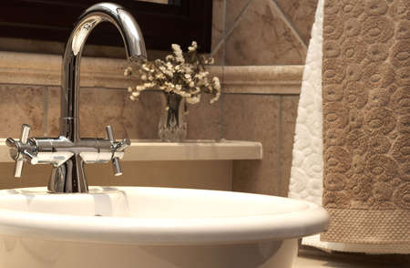 Beautiful sink in a bathroom with beige towels hanging next to it and dry flowers Stock Photo - 3243138