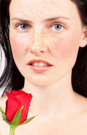Portrait of a beautiful brunette woman with light grey eyes and freckles on her skin holding a red rose photo
