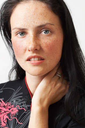 Portrait of a beautiful brunette woman with light grey eyes and freckles on her skin photo