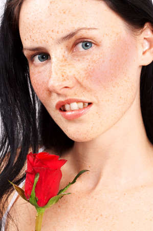 Portrait of a beautiful brunette woman with light grey eyes and freckles on her skin. She is holding a single red rose photo