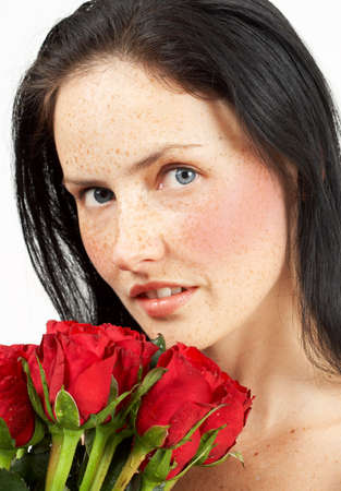 Portrait of a beautiful brunette woman with light grey eyes and freckles on her skin holding a big bouquet with red roses photo