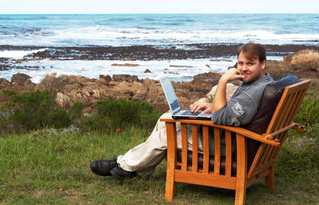 Young handsome businessman working on his laptop by the seacoast, very relaxing working environment photo