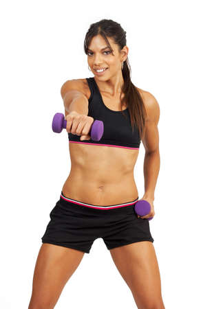 Beautiful brunette woman in gym wear exercising with purple dumbbells