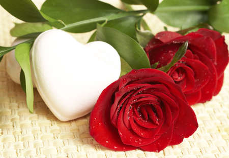 Dark red roses covered with water drops next to pink heart-shaped soap on wooden background.