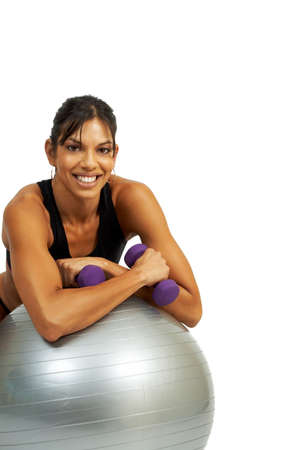 Beautiful brunette woman exercising with purple dumbbells and gym ball