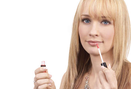 Portrait of a beautiful blonde woman with light blue eyes applying pink lipgloss to her lips Stock Photo - 3299400