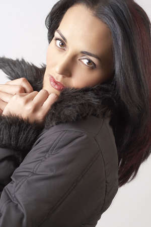 Portrait of a beautiful mature brunette woman with dramatic make-up, wearing winter jacket with fur collar  photo