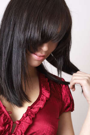 Portrait of a beautiful young brunette woman wearing a red fashionable top playing with her hair