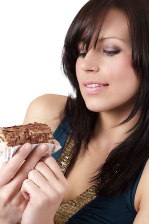 Portrait of a beautiful young brunette woman tempted to eat a chocolate cake photo