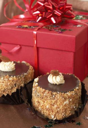 Miniature chocolate con tortas de merengue y crema de almendras y cajas de regalo de color rojo en el fondo  Foto de archivo - 3483647