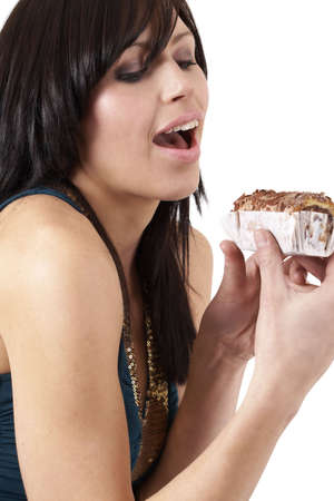 tempted: Portrait of a beautiful young brunette woman tempted to eat a chocolate cake