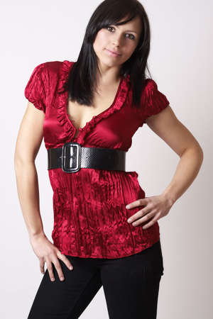 Portrait of a beautiful young brunette woman wearing a red fashionable top with a leather belt and skinny jeans photo