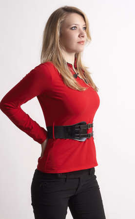 Portrait of beautiful blonde woman wearing a red top with a belt and stylish skinny pants . Not isolated  photo