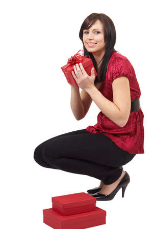 Portrait of a beautiful young brunette woman opening gift boxes at a celebration photo
