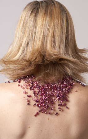 Portrait of a beautiful blonde woman wearing purple pearl necklace sitting with her back to the camera, on grey background photo