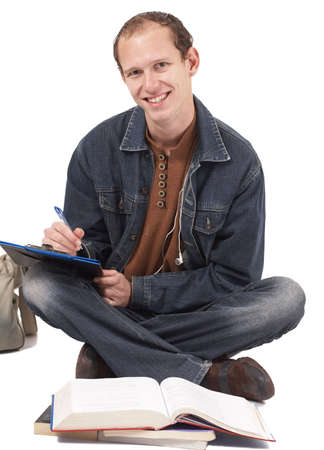 Young male student wearing trendy clothes sitting on the floor studying. Isolated on white background photo