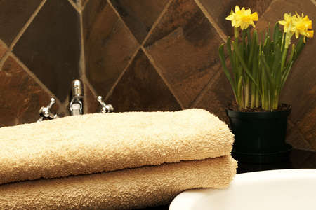 Modern bathroom interior with orange towels lying next to the sink and daffodil flowers Stock Photo - 3657281