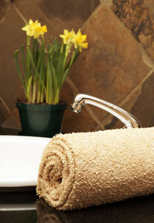 Modern bathroom interior with rolled up towel on the counter and daffodils in the background Stock Photo - 3657280