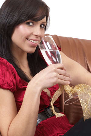 Portrait of a beautiful young brunette woman drinking champagne at a celebration. Isolated on white background photo