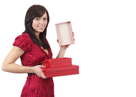 Portrait of a beautiful young brunette woman opening gift boxes at a celebration. Isolated on white background photo