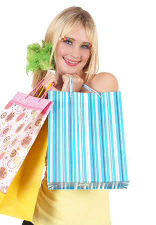 20 25: Portrait of a beautiful blonde woman with light blue eyes and colorful make-up holding shopping bags isolated on white background Stock Photo