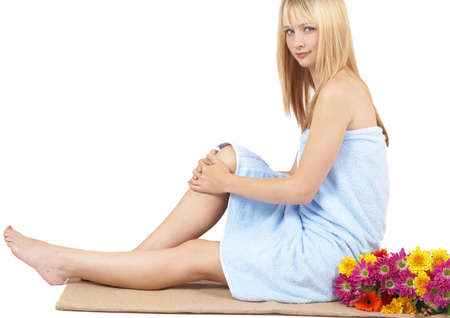 Portrait of a beautiful blonde woman with light blue eyes and natural make-up wrapped in blue towel isolated on white background photo