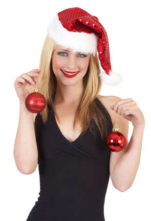 Portrait of a beautiful blonde woman with light blue eyes and colorful make-up wearing red Christmas hat and baubles isolated on white background photo