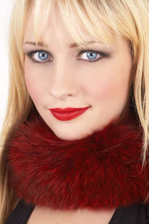 Portrait of a beautiful blonde woman with light blue eyes and bright make-up wearing red fur around her neck on white background Stock Photo - 3916256