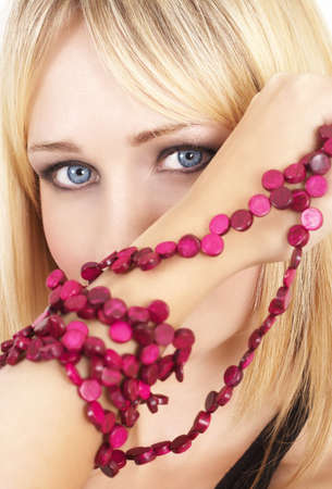 Portrait of a beautiful blonde woman with light blue eyes and dramatic make-up holding pink beads next to her face  photo