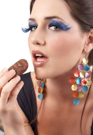 Portrait of a beautiful young brunette woman with dramatic glamour make-up and fashionable earrings holding a chocolate Stock Photo - 3946784