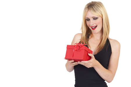 20 25: Portrait of a beautiful blonde woman with light blue eyes and colorful make-up holding a gift box in surprise isolated on white background