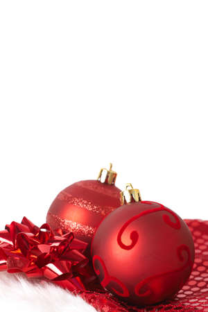 Two red Christmas baubles on Santas hat with red bow isolated on white background with copy space. Shallow depth of field photo