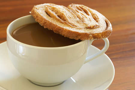 Cup of hot coffee and baked palmier cookie on wooden table background photo
