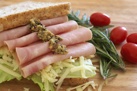 wholegrain mustard: Tasty open sandwich with green lettuce, grated cheese, smoked ham and wholegrain mustard on wholewheat bread with rosemary and tomatoes on chopping board Stock Photo