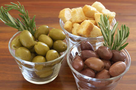 Two jars of green and black olives with stick of rosemary and croutons on wooden table background photo