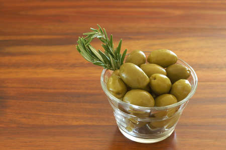 Single jar of green olives with stick of rosemary on wooden table background with copy space photo